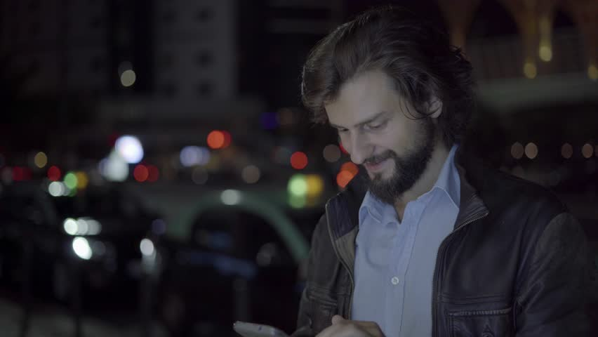 Cheerful man using smartphone in night city. Caucasian smiling freelancer working on smartphone in evening city with empty space. Remote work concept | Shutterstock HD Video #1021055284