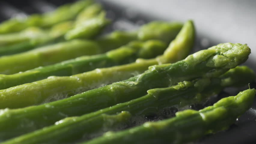 Slide slow motion shot of cooking frozen green asparagus on grill pan