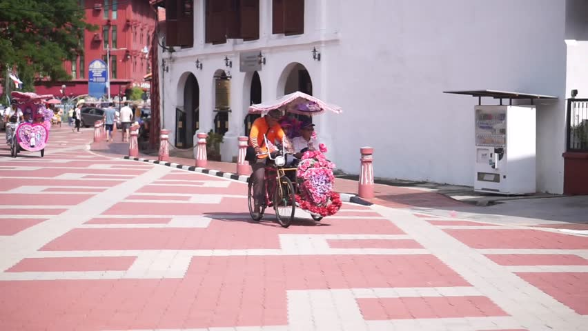 """MALAYSIA, Melacca, November 26, 2018: Tourist rides Trishaw in the Melaka Town. Trishaw or """"beca"""" for the locals, is a traditional transportation right up to the late 1980s and early 1990s."""