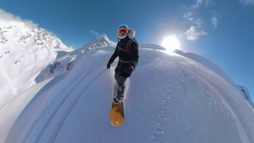 LENS FLARE 360VR: Extreme freerider shredding the un-groomed slopes in the beautiful Canadian backcountry. Female heliboarder enjoying her winter holidays in the pristine mountains of British Columbia
