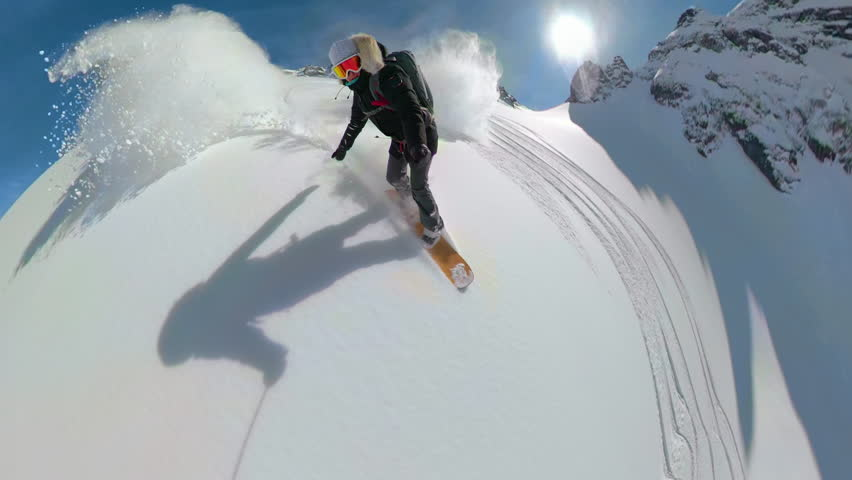 VR360, LENS FLARE: Female snowboarder shredding the un-groomed snowy mountain in breathtaking British Columbia. Unrecognizable woman heliskiing high in the Canadian mountains covered in fresh powder