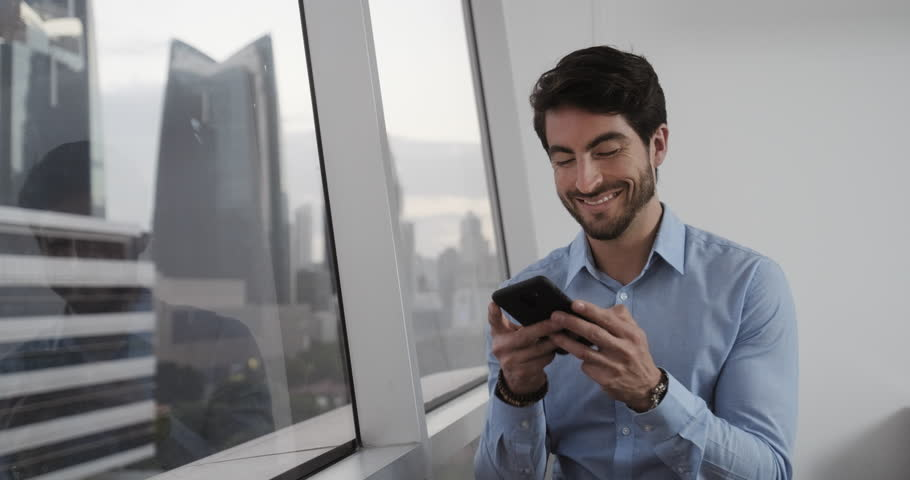 Good looking white ma man at office smiling after sending voice message using his smartphone. Happy Handsome Caucasian Businessman use his phone to send message with app. With Copyspace.