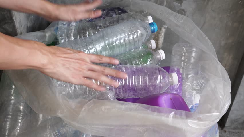 Hand getting plastic bottles to dispose in garbage bag ready to recycle, waste management and plastic recycle | Shutterstock HD Video #1021090219