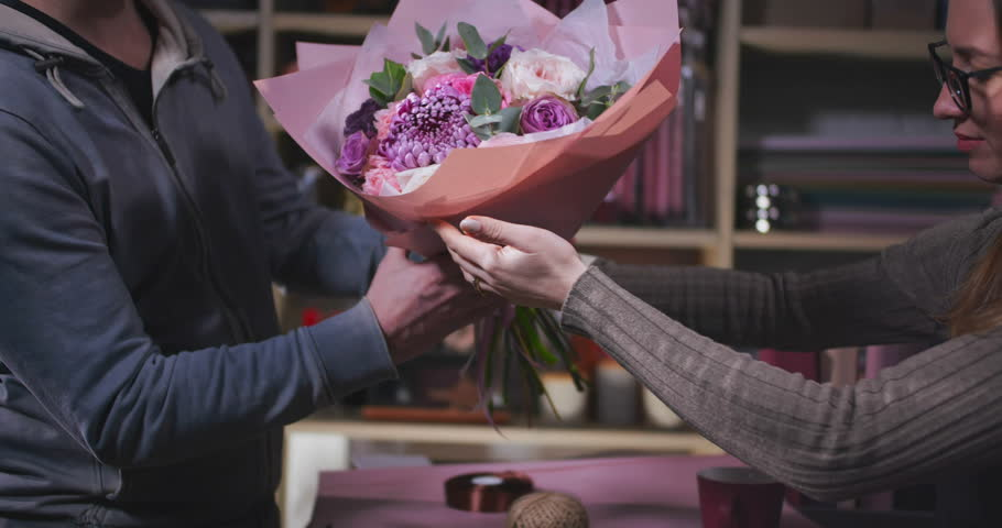 Close up of man buying bouquet of flowers and paying by cash. Florist selling beautiful flowers to a man.