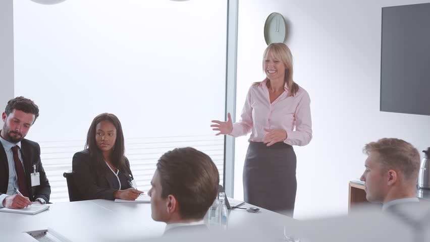 Mature Businesswoman Addressing Group Meeting Around Table At Graduate Recruitment Assessment Day #1021096624
