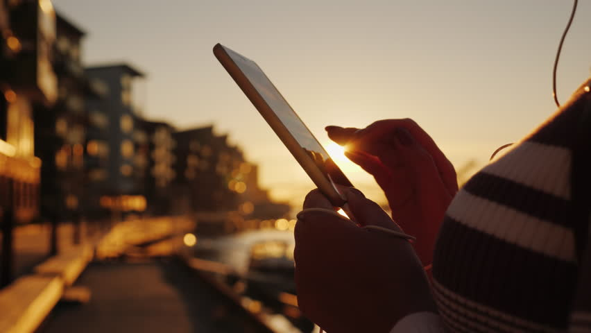 A woman uses a smartphone in an urban setting at sunset. Only hands are visible in the frame, near the pier with yachts | Shutterstock HD Video #1021109836