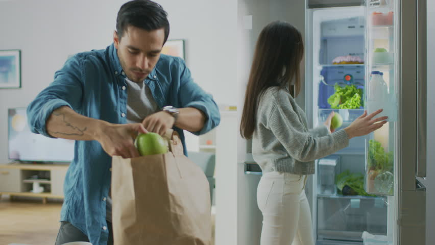 Beautiful Young Couple Come to the Kitchen with Fresh Groceries in Brown Paper Bag. Man is Handing Fresh Salad Greens, Apples and Oranges to the Girl Who Puts Them in the Fridge.