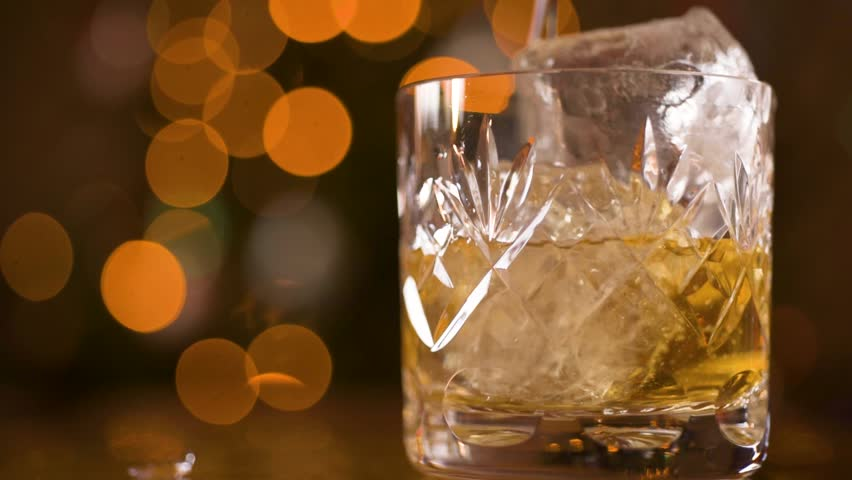 Whiskey Bourbon poured into a glass slow motion ice falling close up macro shot  | Shutterstock HD Video #1021113640