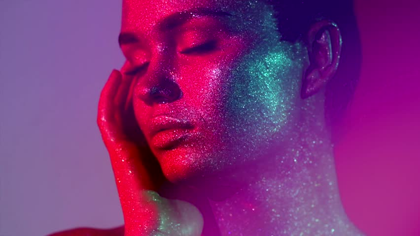 High Fashion model woman in colorful bright sparkles and neon lights posing in studio, portrait of beautiful sexy girl, trendy glowing make-up. Body Art colorful make up. Glitter Vivid makeup 4K