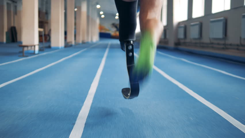 Close up of a male prosthetic leg and a healthy one during jogging