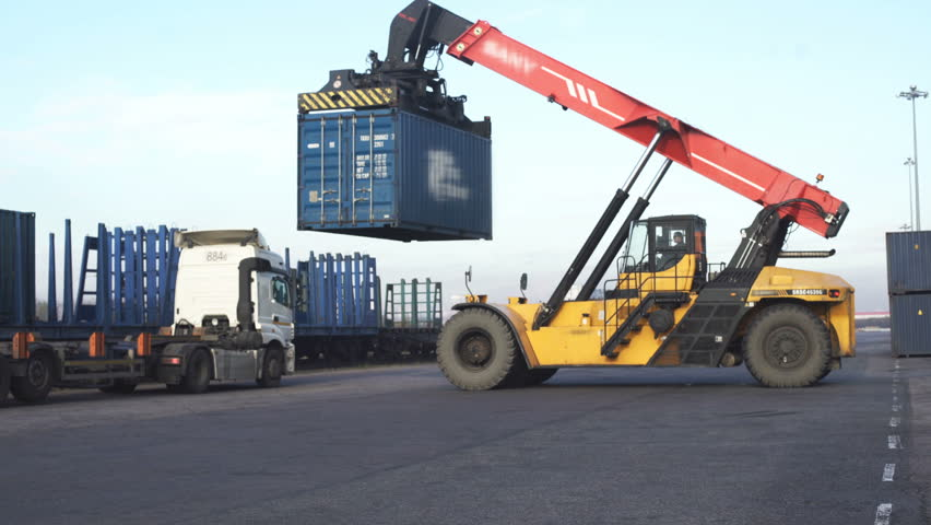Forklift truck lifting cargo container in dock yard against sunrise sky for transportation import, Export and logistic industrial, Business logistic concept, Import and export concept.