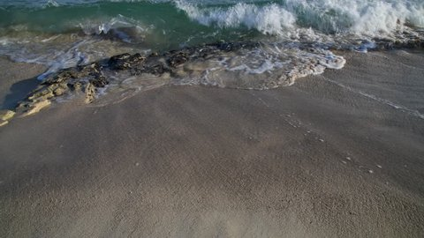 waves of the mediterranean sea splashing about stones and sand