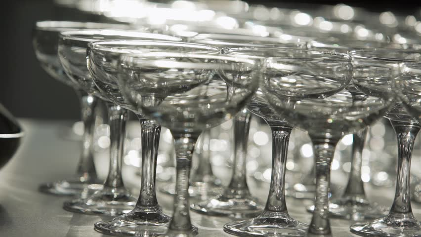 Demonstration of number of rows of clean and shining coctail glasses placed on large grey table in room with dimmed lighting. | Shutterstock HD Video #1021132276