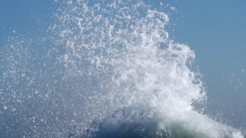 Splashes large strong waves on pier against background of bright blue sky on spring sunny day slow motion. Approaching wave with splashes of water. Strength and power of breaking wave on pier. Splash
