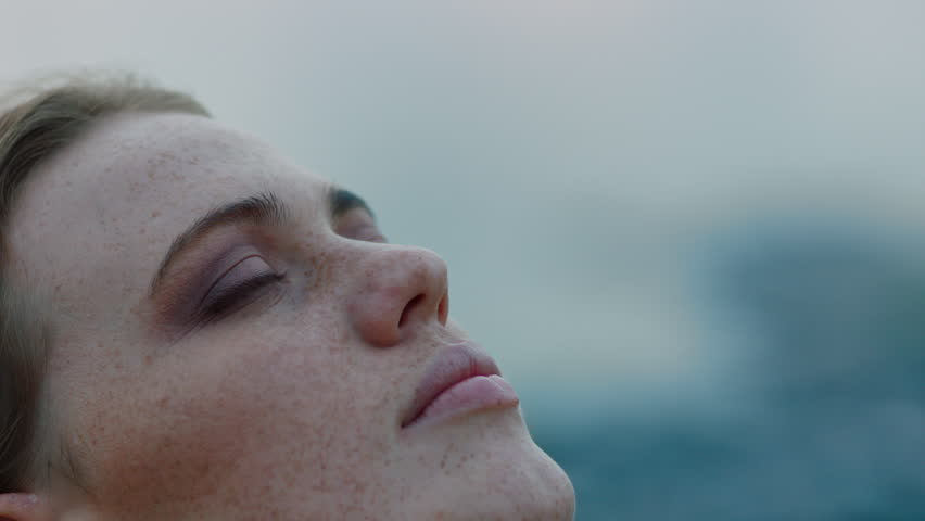 Close up portrait of beautiful young woman looking up praying exploring spirituality contemplating future on cloudy seaside