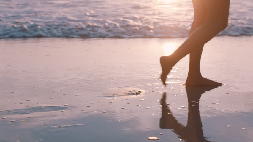 Close up woman feet walking barefoot on beach at sunset enjoying waves splashing gently female tourist on summer vacation | Shutterstock HD Video #1021159702