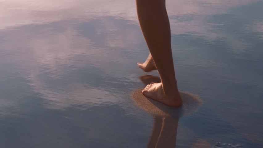 close up woman feet walking barefoot on beach at sunset leaving footprints in sand female tourist on summer vacation