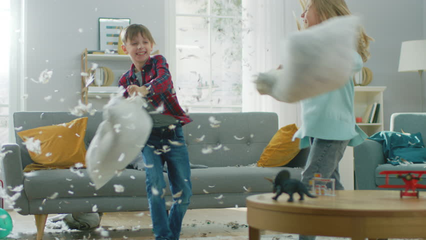 Adorable Little Boy and Sweet Little Girl Have a Pillow Fight in the Sunny Living Room. Siblings Having Fun Fighting with Pillows, Feathers Flying Around. In Slow Motion | Shutterstock HD Video #1021161139