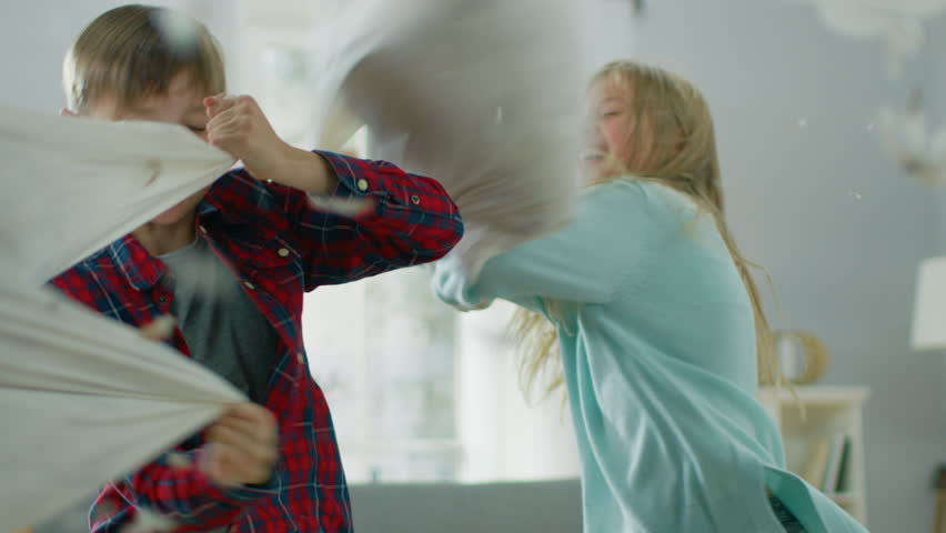 Adorable Little Boy and Sweet Little Girl Have a Pillow Fight in the Sunny Living Room. Siblings Having Fun Fighting with Pillows, Feathers Flying Around. In Slow Motion | Shutterstock HD Video #1021161148