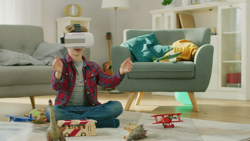 Smart Little Boy Wearing Virtual Reality Headset Uses Hand Gestures to Control Augmented Reality Gameplay. He's Sitting on a Carpet in His Living Room. Happy Child Uses Futuristic AR Glasses at Home. | Shutterstock HD Video #1021161214