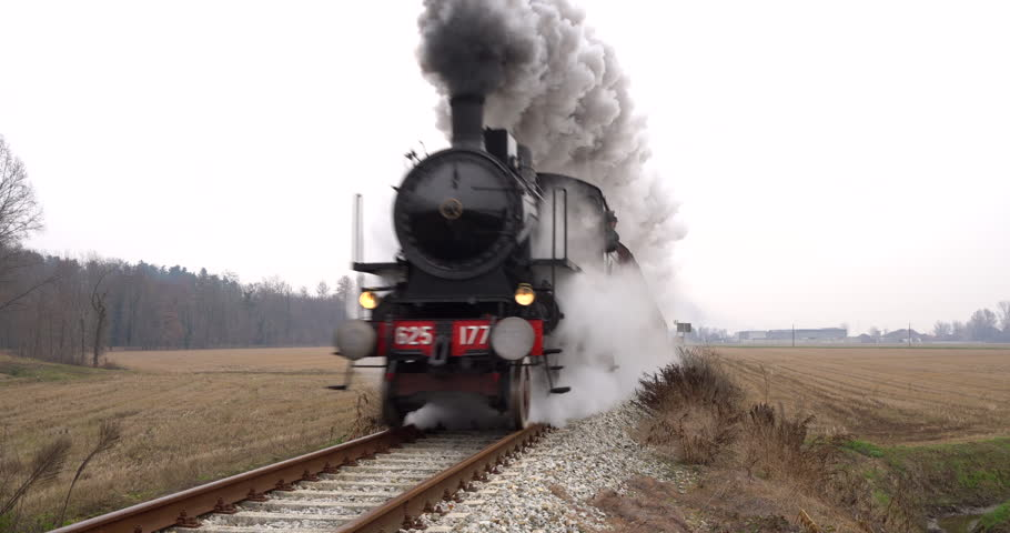Old steam train running on the tracks in the countryside. Heritage historic steam locomotive with white smoke.