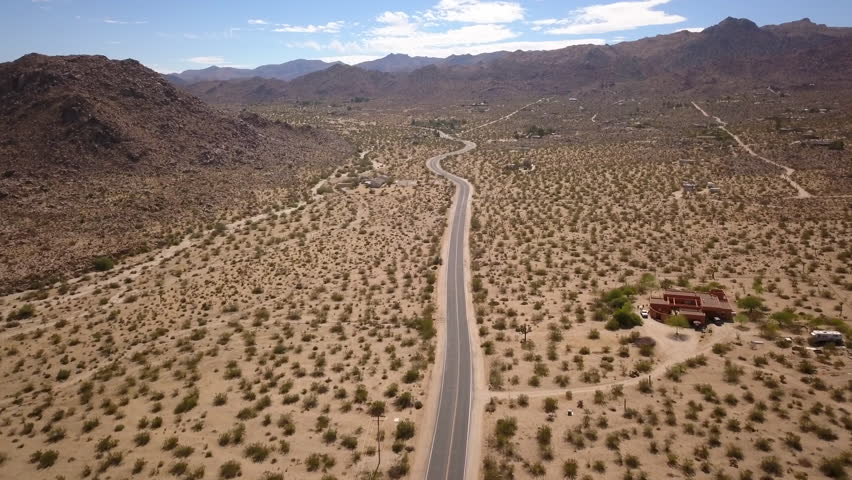 Joshua tree, United States - 10 02 2017: Joshua tree, California - October 2017, aerial shot going forward and ascending above the long road going in the desert to Joshua Tree National park