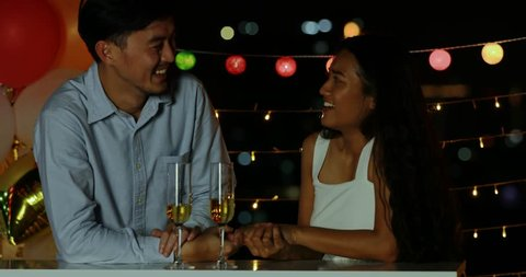 Lovely Asian couple stand and talking, spending their time together, glasses of wine in front of them, in party.