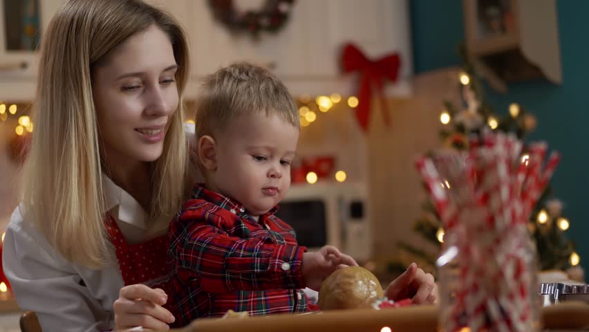 Young beautiful woman and her beautiful baby child make cookies for Christmas at home decorated with attributes of Christmas. Slow motion. Montage. 4K #1021205164