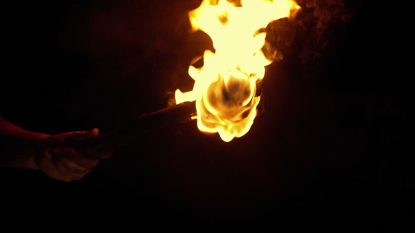 Person Holds Up Burning Torch In The Dark