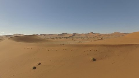 Drone shot of people standing on a dune with the spectacular Namib Desert in the back, view at Deadvlei in Namibia