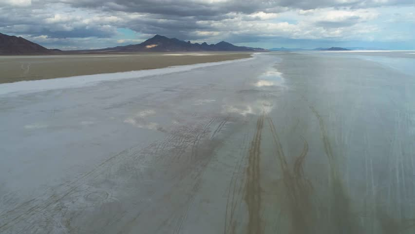 Aerial view of big salt flats with the sky mirroring in them and mountains and clouds in the background