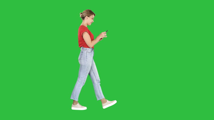 Beautiful young woman walking and reading text message on her mobile phone on a Green Screen, Chroma Key.