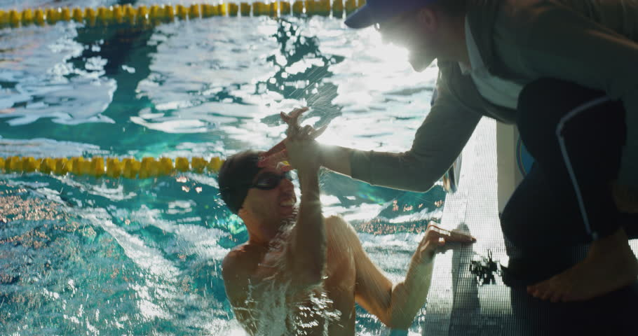 Professional swimmer is encouraged by his coach for new record achievement. Shot with RED Camera in 8K. Concept of sport, swimming pool, competition, fitness. Royalty-Free Stock Footage #1021255333