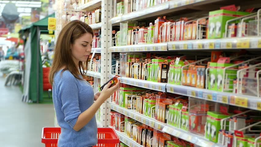 Pretty woman buying ledbulb in supermarket, holding led bulb in hands. Dressed in navy blue sweater Royalty-Free Stock Footage #1021256242