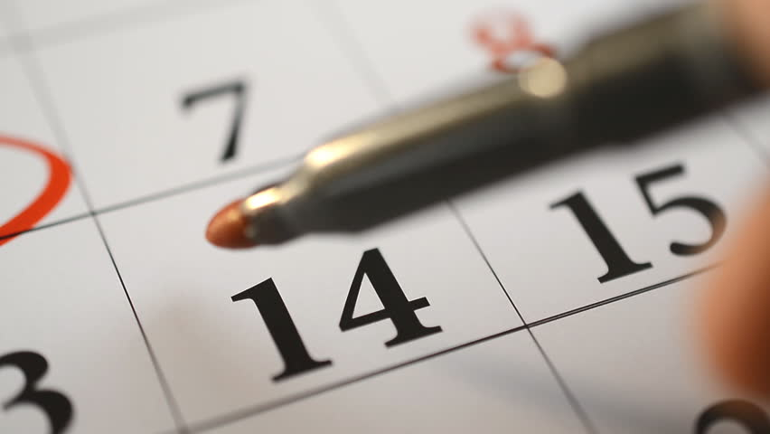 Signing a day on a calendar by red pen, fourteenth of february Valentine's day
