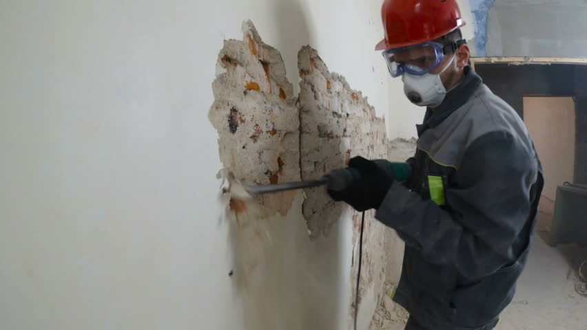 Worker in protective suit demolishes plaster wall. Dirty, hard work. Personal protective equipment. Helmet, respirator and goggles.   Shutterstock HD Video #1021290460