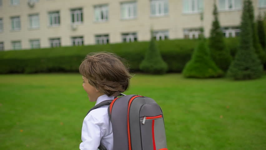 smiling little boy schoolboy student with backpack going and running to school outdoors. First-grade student, primary school, first grader, first class 1 september, kid child children schoolchild Royalty-Free Stock Footage #1021300720