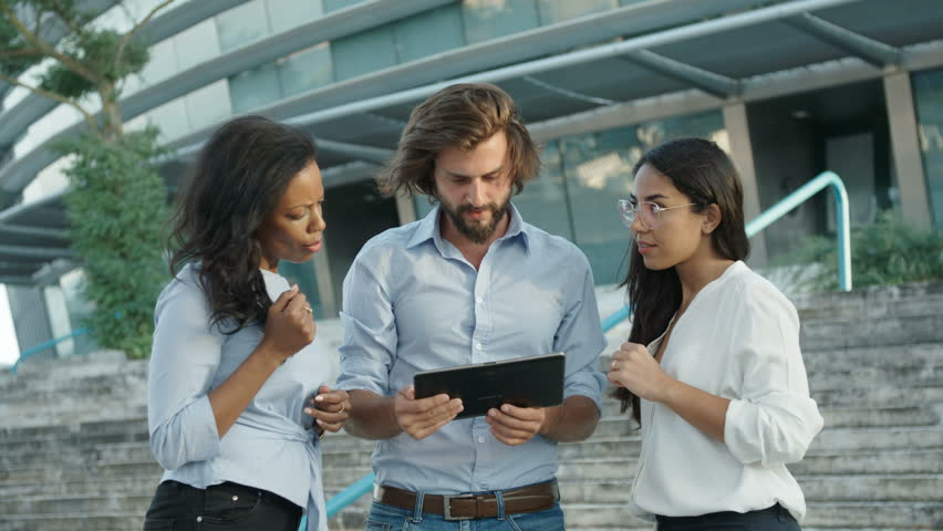 Three young attractive people looking at tablet screen. Serious tall bearded man holding portable computer, showing something to female colleagues, they smiling and laughing.Successful people concept. | Shutterstock HD Video #1021306252