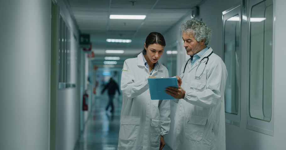 Doctor and nurse discussing the diagnosis of a patient for the future advice for his treatment during walking in a hospital ward. Concept of medicine, technology, health care and people, hospital