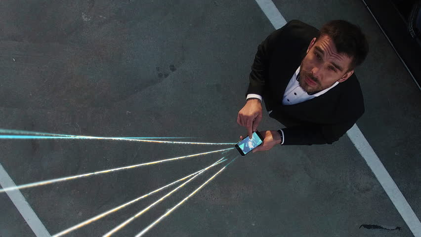 Big City Businessman Uses Smartphone, Stands on Skyscraper Roof: Visualization of Information Flows and Lines Flying from Mobile Phone into Global Network. Top Down Aerial Elevating Drone Shot. Royalty-Free Stock Footage #1021307812