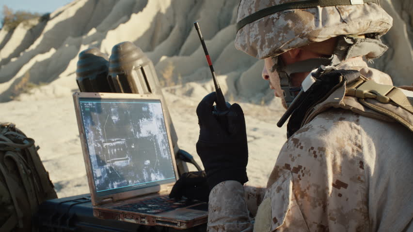Military Operation in the Desert, Using Satellite or Drone Technology: Soldier with Laptop Monitors Movement of Armed Terrorist Vehicle, Uses Radio Communication to Call an Air Strike. | Shutterstock HD Video #1021307821