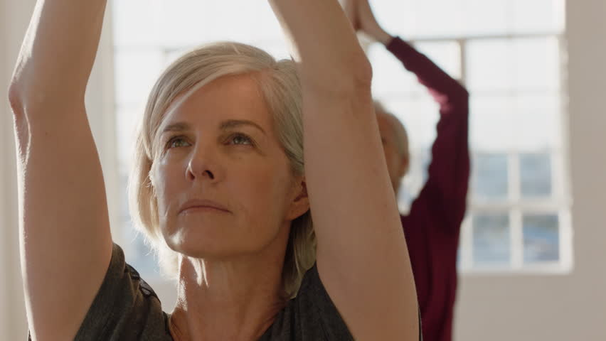yoga class portrait of mature woman exercising healthy lifestyle practicing prayer pose enjoying group physical fitness workout in studio #1021311433