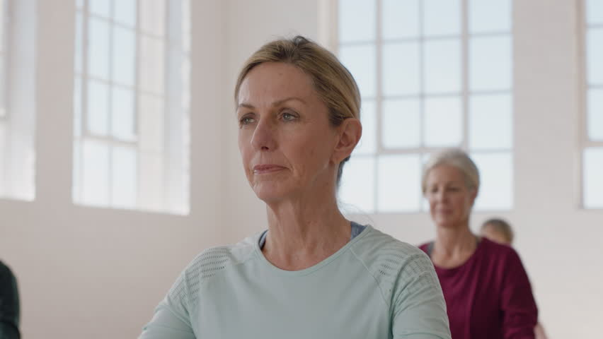 Portrait yoga class beautiful mature woman exercising healthy meditation practicing prayer pose enjoying group physical fitness workout in studio | Shutterstock HD Video #1021312384