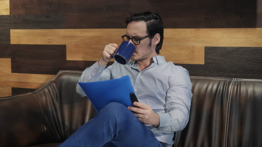Young male manager working in modern office cafeteria. Busy business man drinking coffee at work in corporate coworking space lounge. Businessman, white collar worker, job and career | Shutterstock HD Video #1021319317