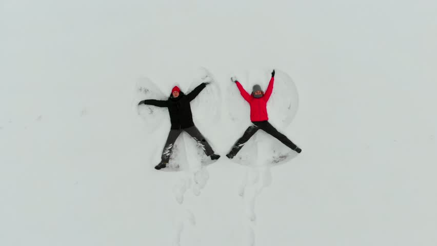 Young couple lying in fresh snow, making snow angels having fun. Aerial video of cheerful young people outdoor in winter.