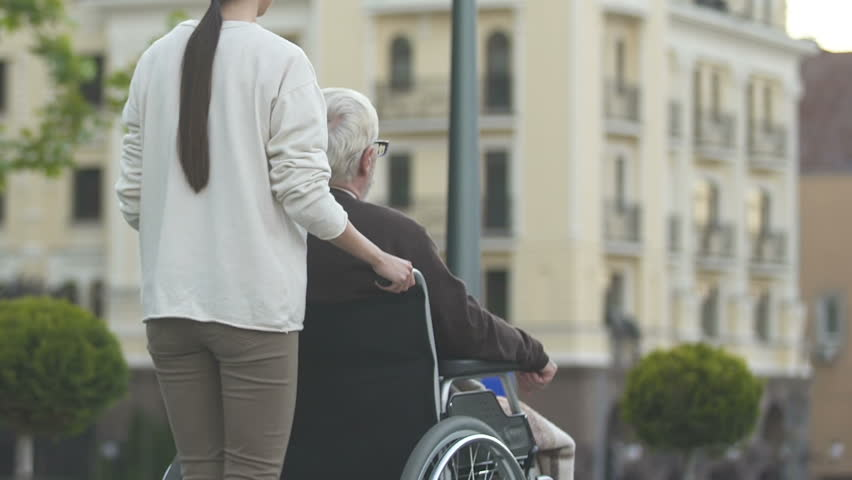 Nurse pushing man in wheelchair, living conditions for disabled people in city | Shutterstock HD Video #1021331311