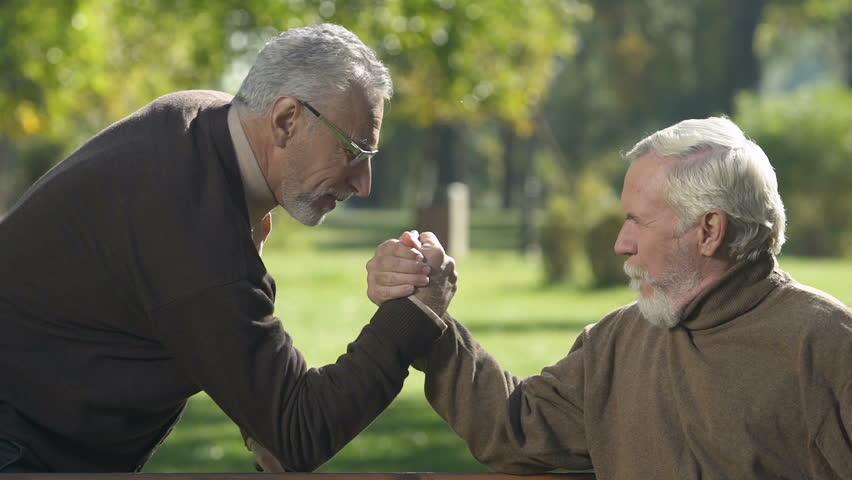 Positive senior men arm-wrestling outside, aged friends having fun together