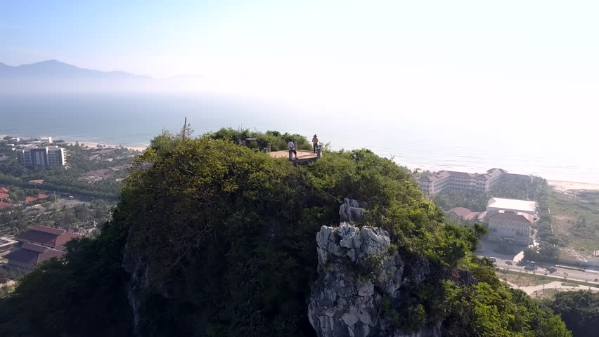 Flycam removes from pictorial mountain top observation deck among trees with distant people against city under blue sky