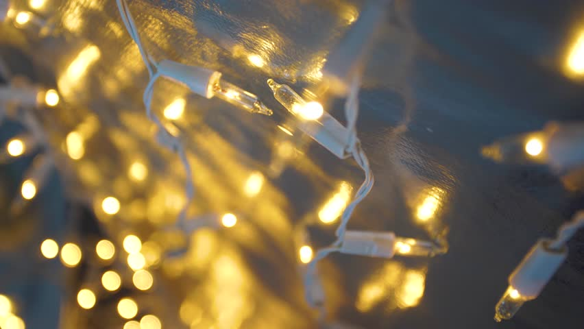 Christmas blurry glowing lights of holiday garland on silver background. Xmas shiny festive decorations for party celebration.  | Shutterstock HD Video #1021362634