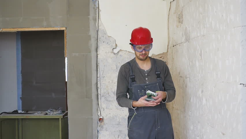 The worker in a construction with helmet counts money euro against the background of the repaired apartment.   Shutterstock HD Video #1021367656